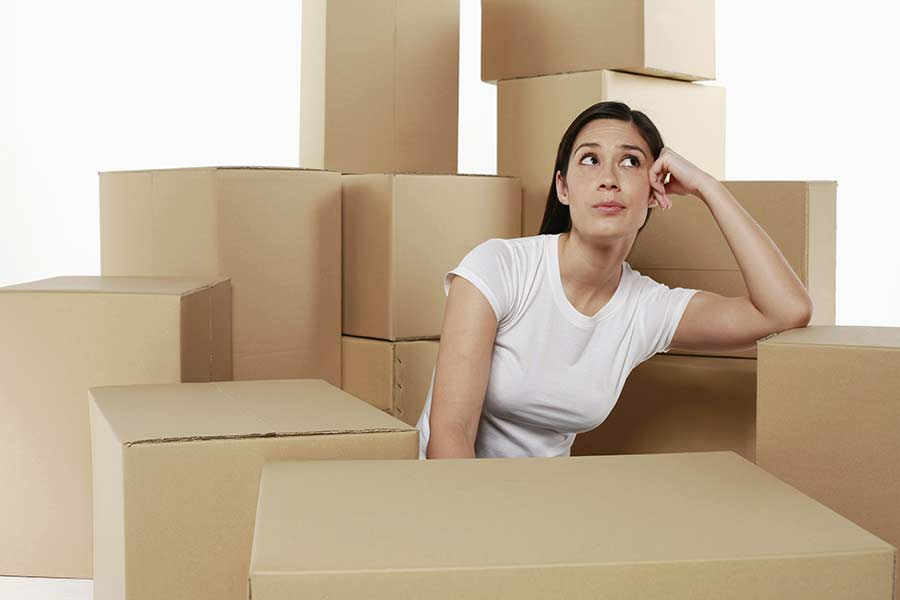 Woman thinking with stacks of boxes