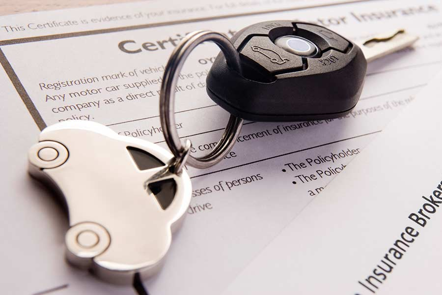 Car keys on top of insurance paperwork